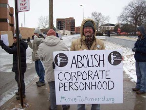 """Top Pun with """"Abolish Corporate Personhood"""" sign in front of federal courhouse in Toledo, Ohio, at Move To Amend protest sponsored by Occupy Toledo"""